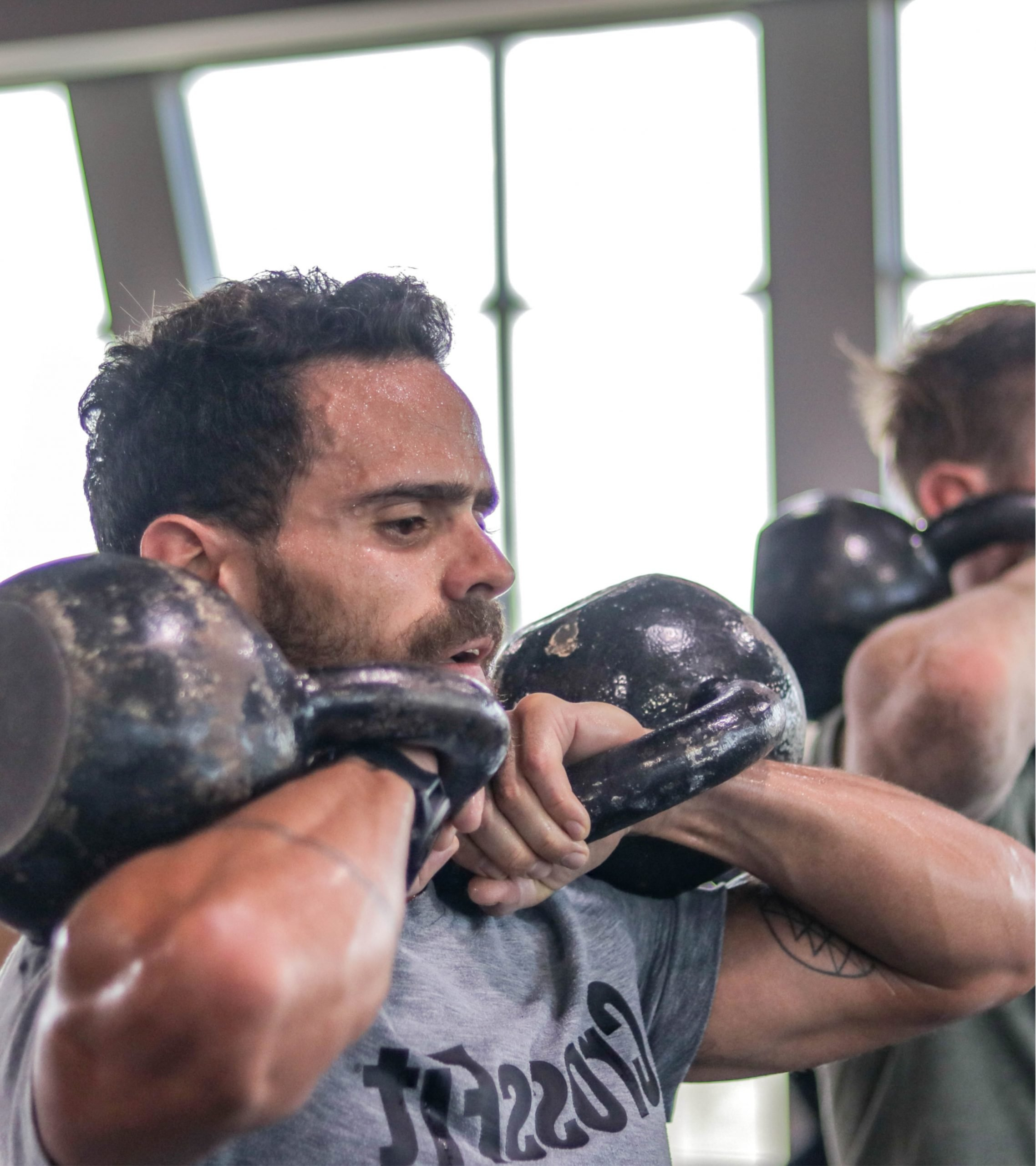 Man Holding two Kettlebells front-hold